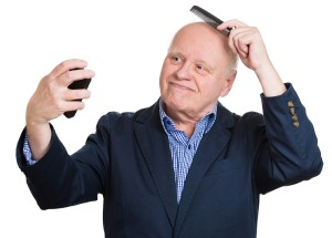 Closeup portrait, senior mature, haughty, arrogant man admiring himself in the mirror combing his bald head, smiling, isolated white background. Human emotions, facial expressions, feelings, attitude